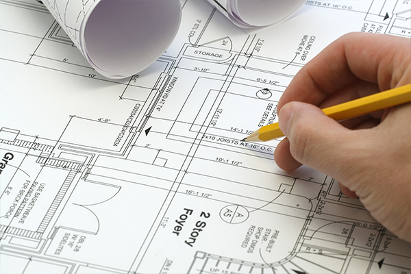 An image of person using a pencil to point at a blueprint of a house