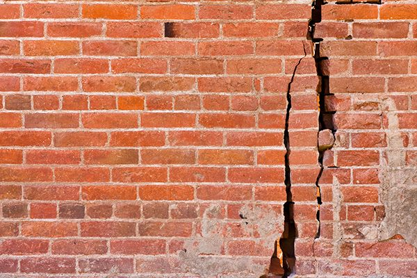 Red brick wall with cracks