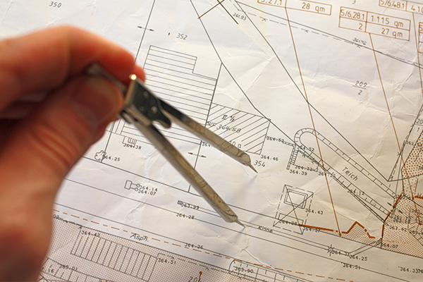 AN image of a surveyor looking over a house blueprint